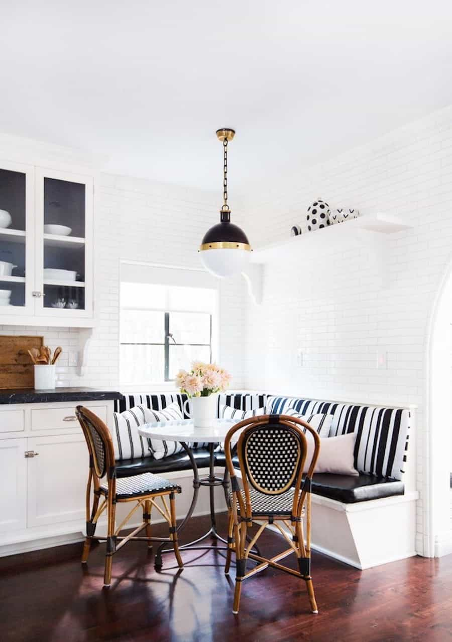Image of white kitchen with black and white designed kitchen and a banquette in the corner near the window.
