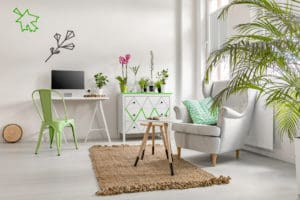 Bright living room interior with home plants, commode and cosy armchair